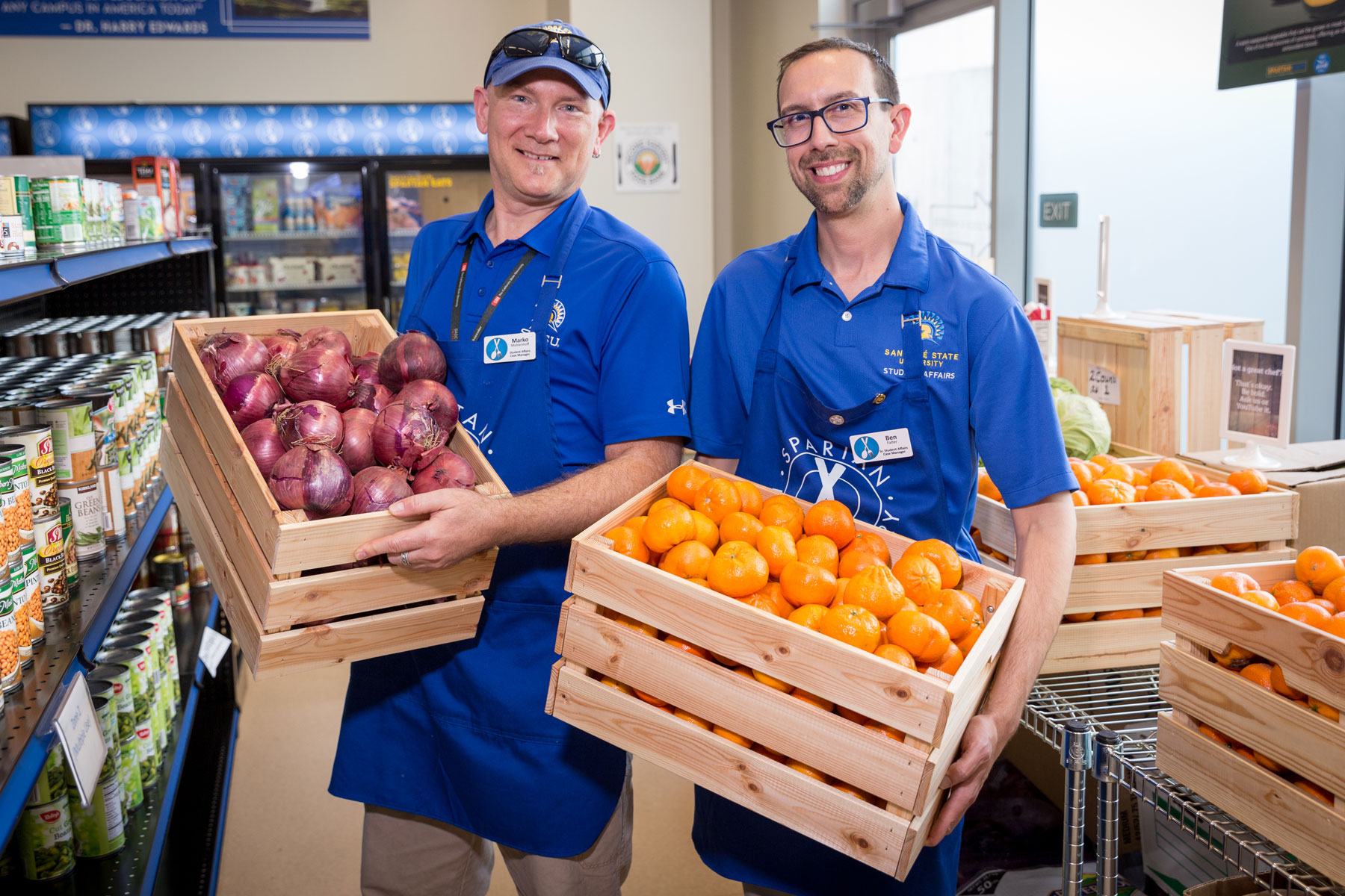 SJSU Cares staff holds fresh produce offerings from the Spartan Food Pantry.