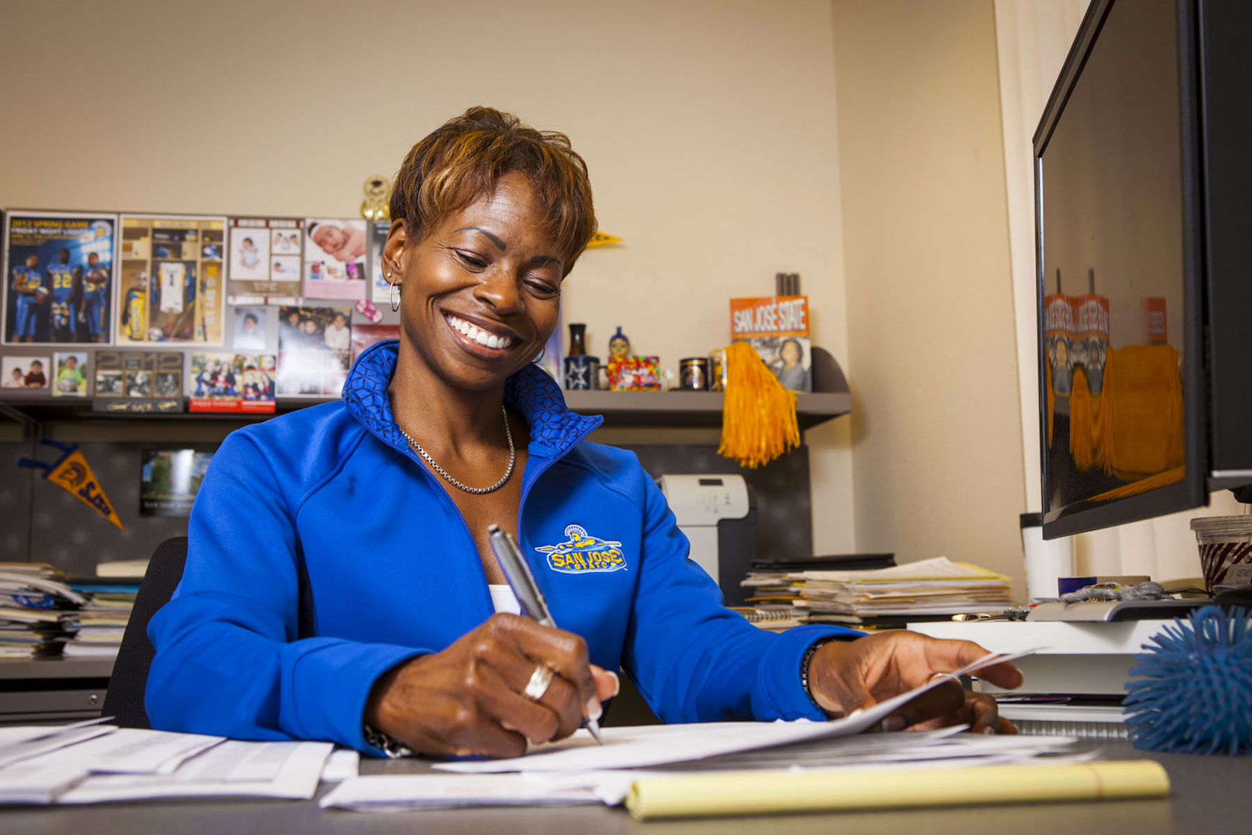 Coleetta McElroy smiling while doing paperwork.