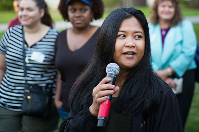 SJSU community member holding a mic and talking.