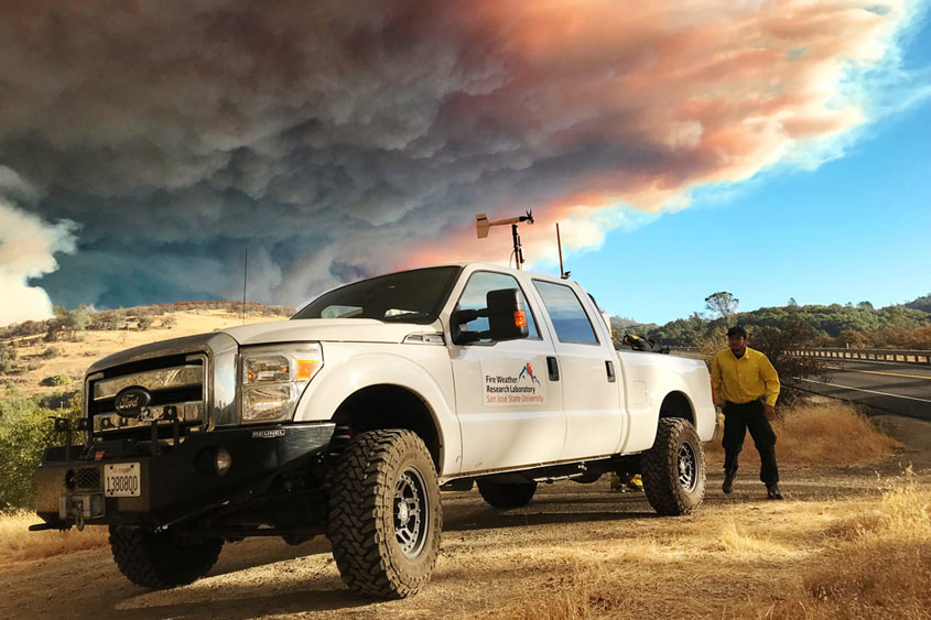Fire weather truck with plumes of smoke in the sky.
